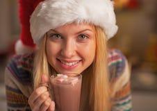 Portrait de fille heureuse dans le chapeau de Santa avec la tasse de chocolat chaud Photos libres de droits