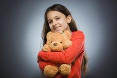 Portrait de fille heureuse jouant avec l'ours de nounours d'isolement sur le gris photographie stock libre de droits