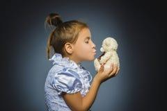 Portrait de fille heureuse jouant avec l'ours de nounours d'isolement sur le gris photos stock