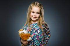 Portrait de fille heureuse jouant avec le chien de jouet d'isolement sur le gris Images stock