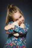 Portrait de fille heureuse jouant avec le chien de jouet d'isolement sur le gris Image stock