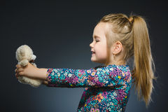 Portrait de fille heureuse jouant avec le chien de jouet d'isolement sur le gris Images libres de droits