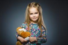 Portrait de fille heureuse jouant avec le chien de jouet d'isolement sur le gris Photos libres de droits