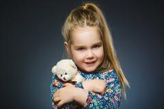 Portrait de fille heureuse jouant avec le chien de jouet sur le gris Photo stock