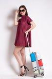 Portrait de fille heureuse partant en vacances marchant avec la valise et le sourire Image stock