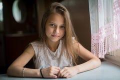 Portrait de fille mignonne se reposant à la table Photos libres de droits