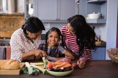 Portrait de fille préparant la nourriture avec la mère et la grand-mère dans la cuisine Images stock