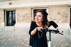 Portrait de fille souriant et montant le scooter électrique Photographie stock