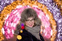 Portrait de fille de sourire joyeuse gaie dans un chapeau de fourrure d'hiver dans la perspective de l'illumination de nuit penda image libre de droits