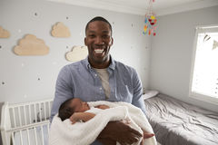Portrait de fils de Holding Newborn Baby de père dans la crèche Photographie stock libre de droits