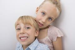 Portrait de frère heureux avec la soeur au-dessus du fond gris Image stock