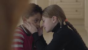 Portrait de garçon adorable mignon d'afro-américain et de fille caucasienne assez blonde touchant des fronts Enfants banque de vidéos