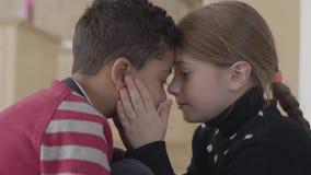 Portrait de garçon adorable mignon d'afro-américain et de fille caucasienne assez blonde touchant des fronts prise de fille clips vidéos