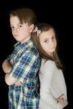 Portrait de garçon avec les bras pliés et la fille avec des mains sur ses hanches Image libre de droits