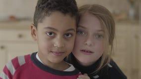 Portrait de gar?on beau d'afro-am?ricain et de fille caucasienne assez blonde ayant se reposer ensemble dans la cuisine banque de vidéos
