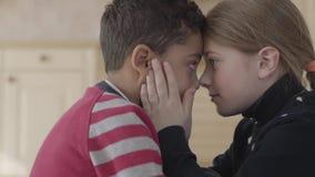 Portrait de gar?on beau d'afro-am?ricain et de fille caucasienne assez blonde touchant des fronts Enfants banque de vidéos