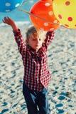 Portrait de garçon caucasien blanc drôle d'enfant d'enfant avec le groupe coloré de ballons, jouant le fonctionnement sur la plag Photographie stock