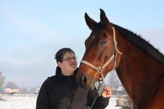 Portrait de garçon d'adolescent et de cheval de baie en hiver Images libres de droits