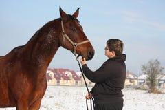 Portrait de garçon d'adolescent et de cheval de baie en hiver Photos libres de droits