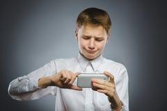 Portrait de garçon d'offense avec le mobile ou le téléphone portable Émotion humaine négative image libre de droits