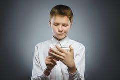 Portrait de garçon d'offense avec le mobile ou le téléphone portable Émotion humaine négative photos stock