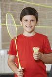 Portrait de garçon dans le gymnase d'école jouant le badminton Photo stock
