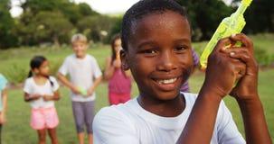 Portrait de garçon de sourire jouant avec l'arme à feu d'eau banque de vidéos