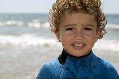 Portrait de garçon espiègle sur la plage avec la mer sur le fond Images stock