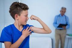 Portrait de garçon fléchissant son biceps dans la clinique Photographie stock