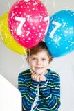 Portrait de garçon heureux d'enfant avec le groupe sur les ballons à air colorés sur l'anniversaire 7 Photo stock