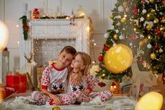 Portrait de garçon heureux riant dans son étreinte de soeur la soirée de Noël photo libre de droits