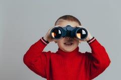 Portrait de garçon de sourire attirant dans le chandail rouge regardant par le plan rapproché noir de jumelles photo stock