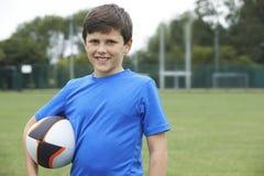 Portrait de garçon tenant la boule sur le lancement de rugby d'école photographie stock