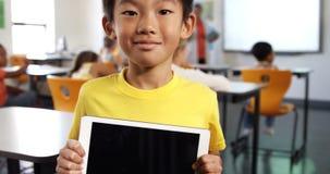 Portrait de garçon tenant le comprimé numérique dans la salle de classe clips vidéos