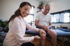 Portrait de genou de examen de thérapeute féminin de patient masculin supérieur avec le marteau réflexe Images libres de droits