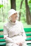 Portrait de grand-mère heureuse sur un banc de parc, photographie stock libre de droits