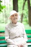 Portrait de grand-mère heureuse sur un banc de parc, photo libre de droits