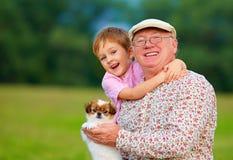 Portrait de grand-papa, de petit-fils et de chiot heureux Image stock