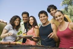 Portrait de groupe des amis occasionnels appréciant un barbecue Image stock