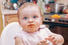 Portrait de jeune bébé heureux dans la chaise d'arbitre étant alimentée photo stock