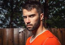 Portrait de jeune bel homme dans l'orange, sur le fond extérieur Photographie stock libre de droits
