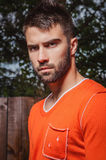 Portrait de jeune bel homme dans l'orange, sur le fond extérieur Image libre de droits