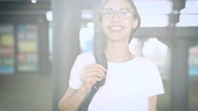 Portrait de jeune belle femme à la mode de sourire dans l'eyewear transparent posant dehors Mouvement lent banque de vidéos