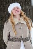 Portrait de jeune belle femme dans le manteau se penchant de nouveau au tronc d'arbre avec les yeux fermés dans le jardin d'hiver Images libres de droits