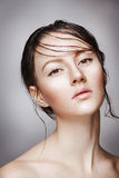 Portrait de jeune belle femme nue avec le maquillage brillant humide sur le fond gris photos libres de droits
