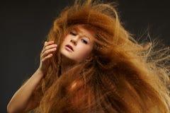 Femme rousse bouclée aux cheveux longs Image stock