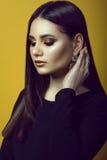 Portrait de jeune belle fille aux cheveux foncés avec le maquillage professionnel dans des couleurs d'or et de cuivre cachant ses photo libre de droits