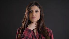 Portrait de jeune belle fille aux cheveux longs dans la douleur plaided de chemise de l'angine terrible sur le fond noir image stock
