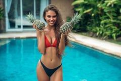 Portrait de jeune belle fille de brune dans le maillot de bain avec l'ananas en son fruit de mains jugeant dessus le sein sexy image libre de droits