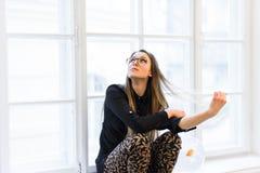 Portrait de jeune belle fille d'étudiant en verres avec les poissons d'or sur le rebord de fenêtre blanc images libres de droits